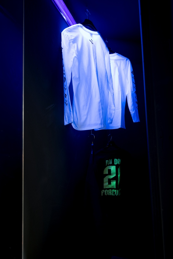 ∞ Doi Doi merchandise hanging inside false wall – #SMLXL Long sleeve T-shirt and #21Forever glow in the dark jersey sweatshirt ∞